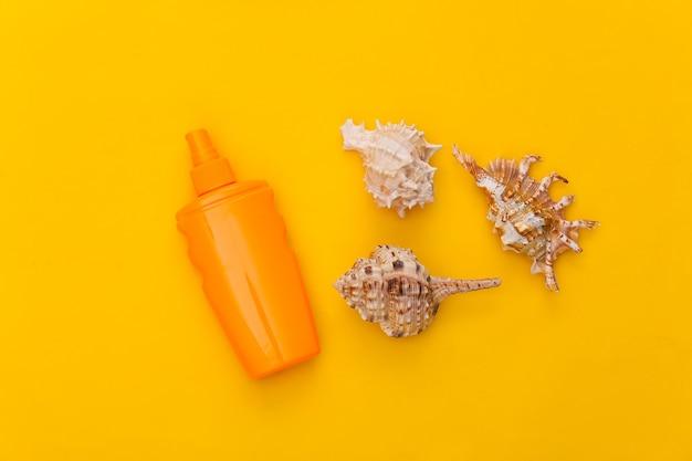Butelka z filtrem przeciwsłonecznym i muszla na żółto. ochrona skóry. wakacje na plaży