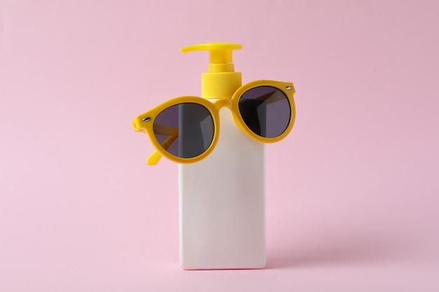 Butelka z filtrem przeciwsłonecznym i okulary na różowym tle na białym tle
