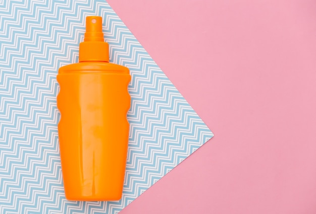 Butelka z filtrem przeciwsłonecznym na różowym niebieskim pastelu. ochrona skóry. wakacje na plaży