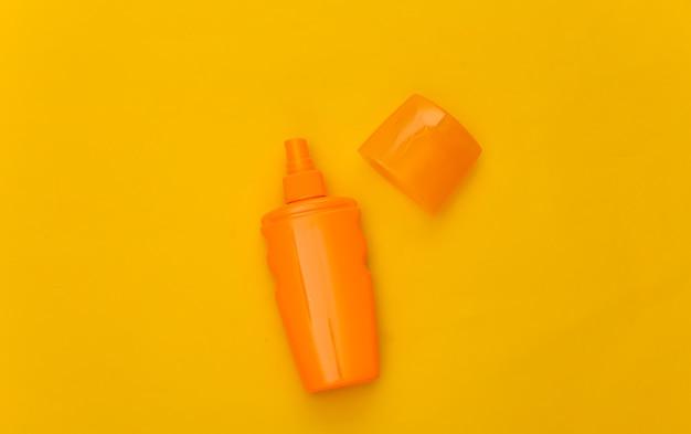 Butelka z filtrem przeciwsłonecznym na żółto. ochrona skóry. wakacje na plaży