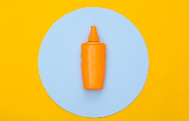Butelka z filtrem przeciwsłonecznym na żółto z niebieskim kółkiem. ochrona skóry. wakacje na plaży