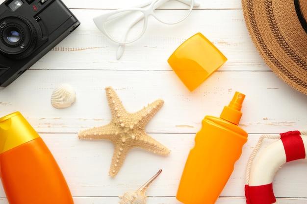 Butelka z filtrem przeciwsłonecznym z kapeluszem, okularami i innymi akcesoriami