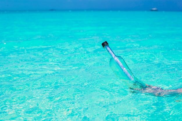 Butelka z komunikatem w dłoni na morzu