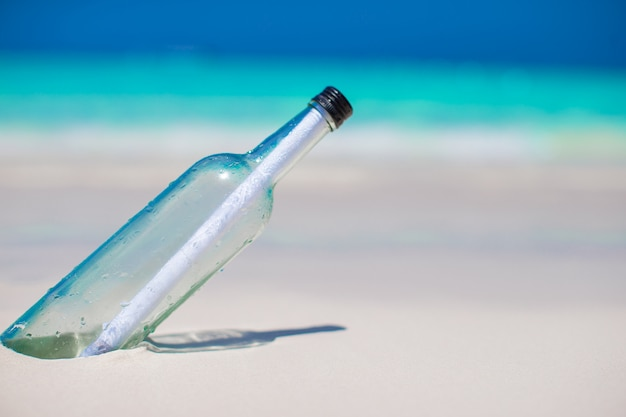 Butelka z komunikatem zakopanym w białym piasku