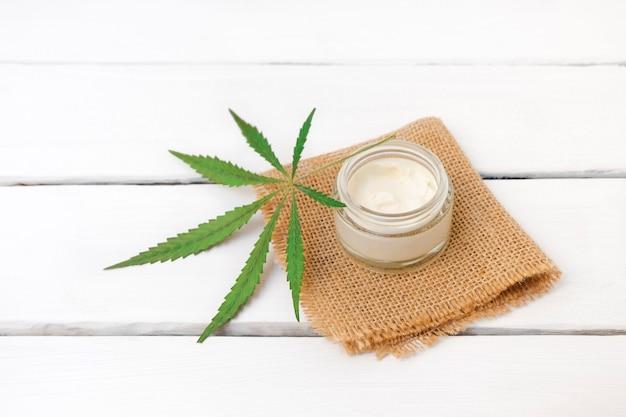Butelka z kremem z konopi indyjskich na białym drewnianym tle z miejscem na kopię liści marihuany