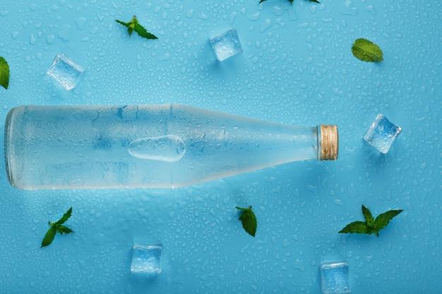 Butelka z lodowatym napojem, kostkami lodu, kroplami i listkami mięty