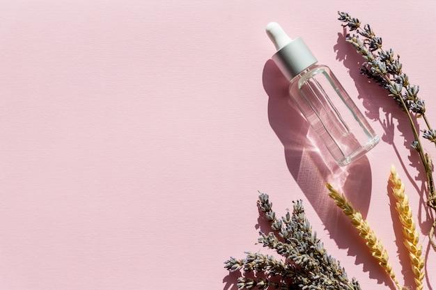 Butelka z olejkiem aromatycznym i kwiatami lawendy. olejek lawendowy do pielęgnacji ciała. aromaterapia, spa, naturalna opieka zdrowotna