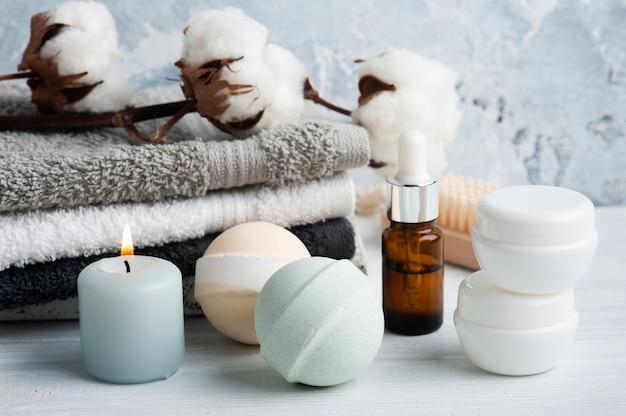 Butelka z olejkiem i aromatyczne kule do kąpieli w kompozycji spa z suchymi kwiatami i ręcznikami