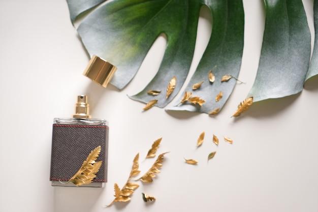 Butelka z perfumami i zielonym tropikalnym liściem na białym tle