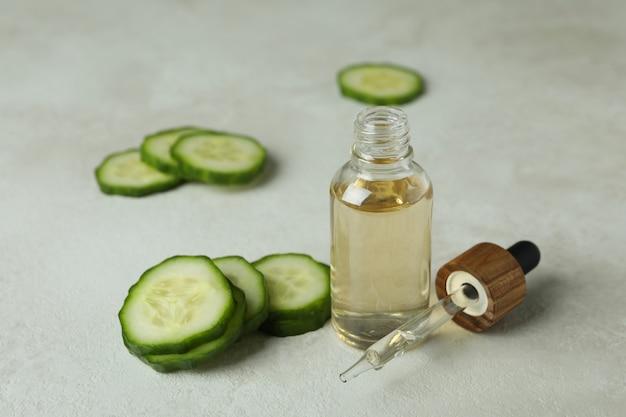 Butelka z plastrami oleju i ogórka na białej powierzchni teksturowanej