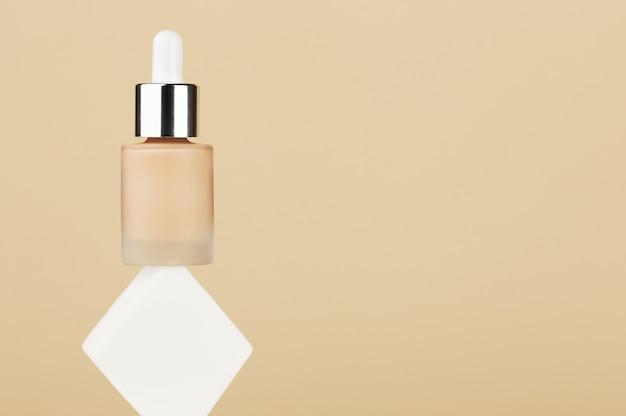 Butelka z płynnym podkładem balansowym w płynie beżowym na białej kwadratowej gąbce. profesjonalny produkt do makijażu dla idealnej cery. akcesoria dla kobiet, bazowy kosmetyk, podkład, korektor. skopiuj miejsce.