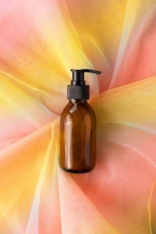 Butelka z pompką na kosmetyk na kolorowej tęczowej tkaninie z organzy. makieta pojemnika z dozownikiem na kosmetyki płynne. koncepcja higieny pielęgnacji skóry w opiece zdrowotnej
