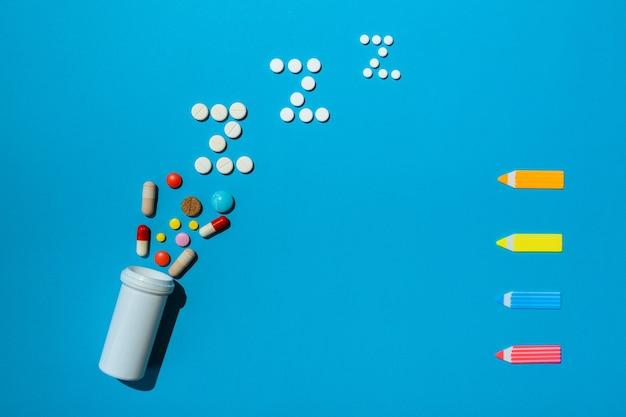 Butelka z różnymi rodzajami tabletek nasennych z wolnym miejscem na tekst przepisu na kurację