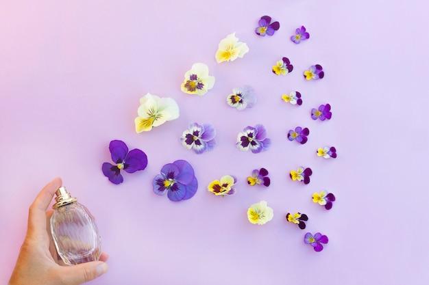 Butelka z rozpylaczem perfum w dłoni ze świeżym kwiatowym aromatem i kwiatami