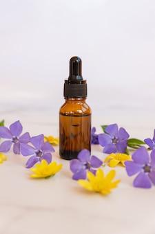 Butelka z serum na marmurowym stole, na powierzchni kwitnące letnie kwiaty