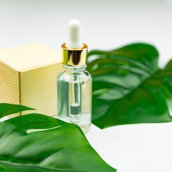 Butelka z surowicą w pobliżu liścia palmowego. modny kosmetyk dla młodej skóry. dodatkowy krok nawilżający w codziennej pielęgnacji twarzy. skopiuj miejsce.