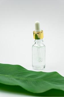 Butelka z surowicą w pobliżu liścia palmowego.