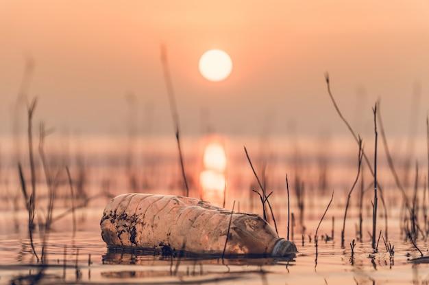 Butelka z tworzywa sztucznego w jeziorze na świeżym powietrzu w upalny dzień z wschodem słońca rano