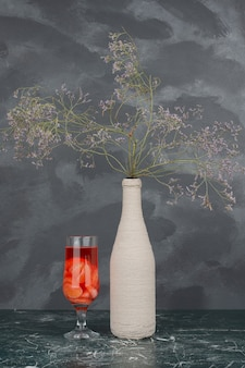 Butelka z uschniętymi kwiatami i szklanką soku na marmurowej ścianie.