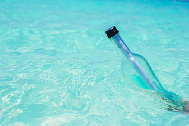 Butelka z wiadomością w ręki tła niebieskim niebie