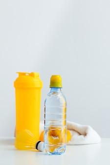 Butelka z wodą i shaker z białkiem. napoje sportowe