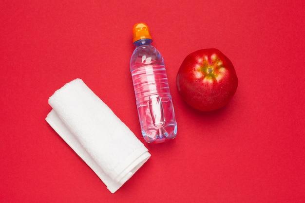 Butelka z wodą leżał płasko widok z góry na kolorowym papierze