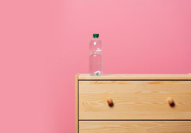 Butelka z wodą na drewnianym stoliku nocnym