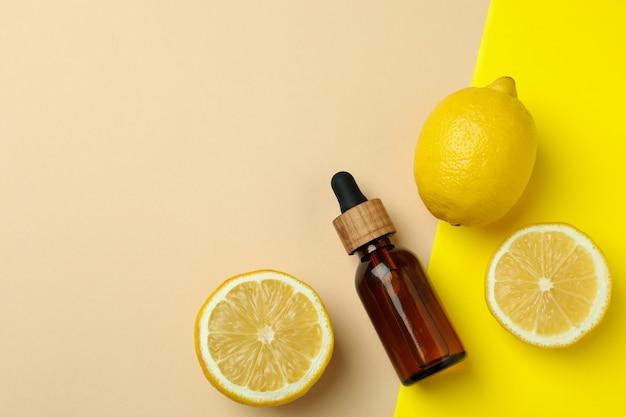 Butelka z zakraplaczem z olejem i cytrynami na tle na białym tle dwóch tonów