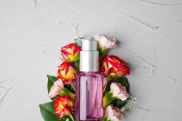 Butelka zapachu lub olejku aromatycznego w wiązce świeżych kwiatów