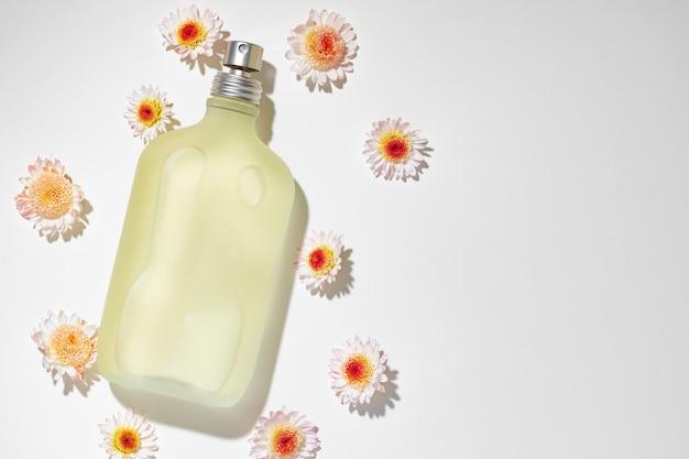 Butelka zapachu otoczona pąkami kwiatowymi z bliska