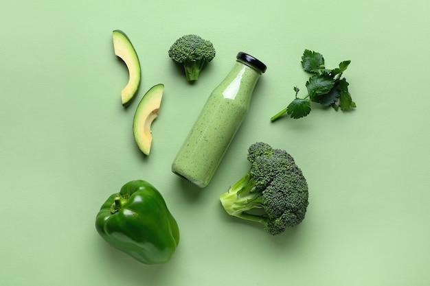 Butelka zdrowego smoothie z awokado i brokułami na kolorowej powierzchni