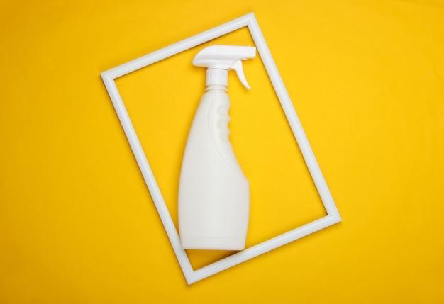 Butelka ze sprayem do mycia szyb na żółtej powierzchni z białą ramką