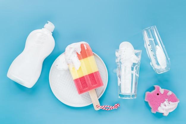 Butelka ze środkiem myjącym i gąbką w postaci lodów i szkła na tle mydlanej pianki. koncepcja mycia naczyń. leżał płasko, widok z góry.
