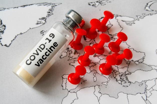 Butelka ze szczepionką chroniąca przed covid-19 na mapie europy za pomocą czerwonych pinezek, gdzie występuje epidemia covid-19