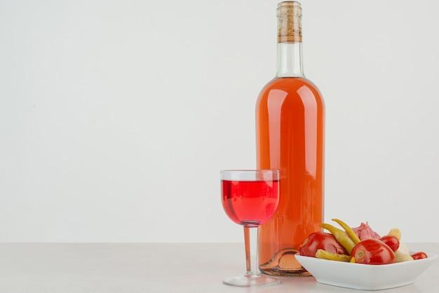 Butelka ze szklanką lemoniady i talerz pierogów.