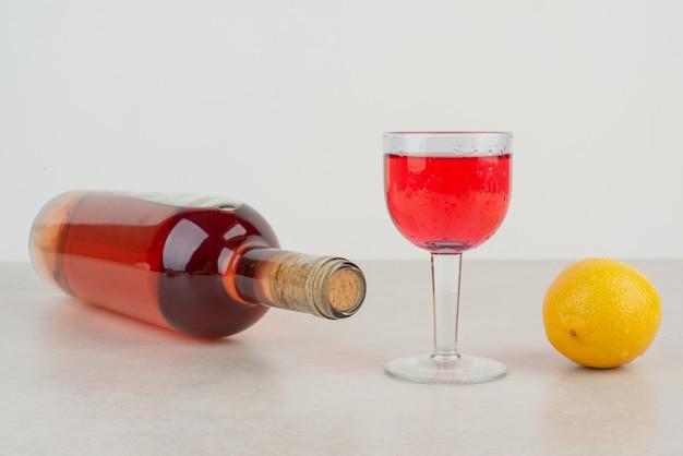 Butelka ze szklanką lemoniady z cytryną.