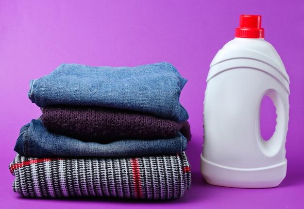 Butelka żelu do prania na stosie ubrań na fioletowym stole.