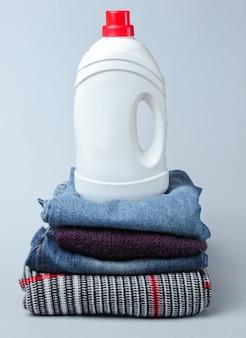 Butelka żelu do prania na stosie ubrań na szarym stole.