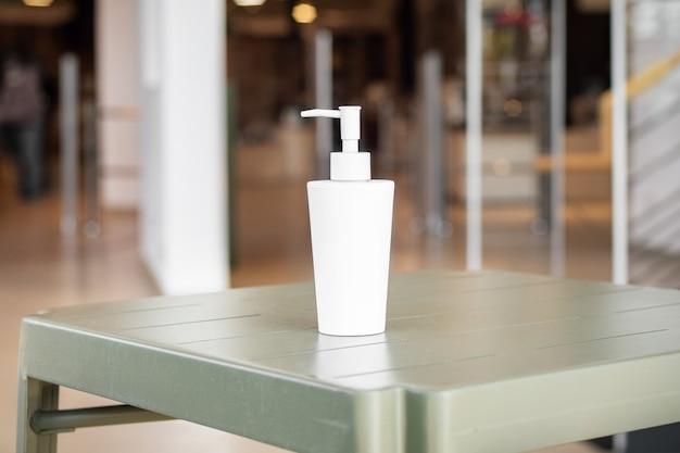 Butelka żelu wodno-alkoholowego przy wejściu do sklepu podczas pandemii koronawirusa.