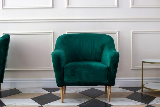 Butelka zielony fotel vintage w pobliżu białej ściany. krzesło welurowe w kolorze butelkowej zieleni