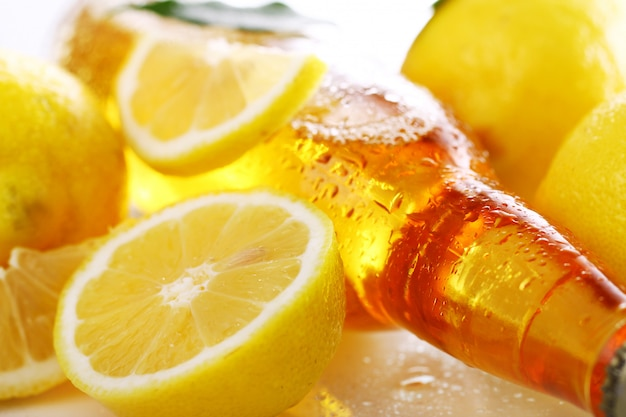 Butelka zimnego piwa ze świeżymi cytrynami
