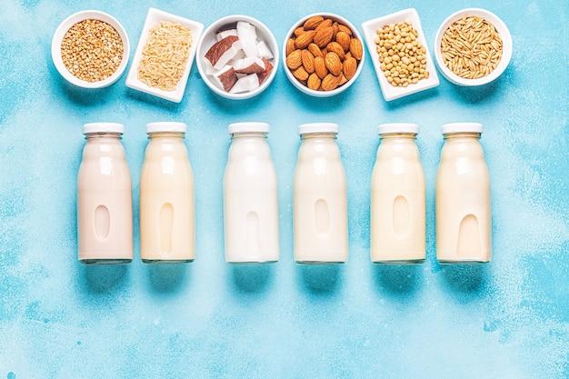 Butelki alternatywnego mleka i składników, widok z góry.