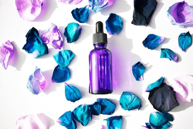 Butelki aromatycznego oleju z niebieskimi płatkami róży. podstawy aromaterapii. widok z góry. botaniczna pielęgnacja skóry w domu zabiegi spa.