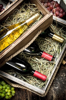 Butelki czerwonego i białego wina w starych pudełkach na drewnianym stole.