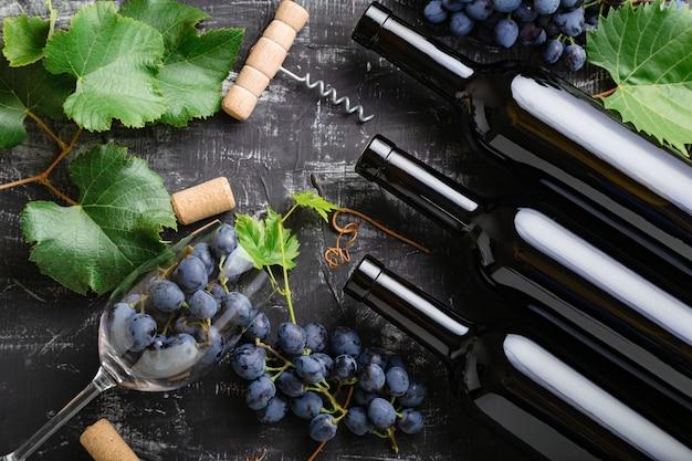 Butelki czerwonego wina winogrona, kiście winogron, liście i winorośli korkociąg korki kieliszki do wina na ciemnym tle rustykalnym betonu. skład wina na stole czarnej kredy kamiennej. widok z góry.