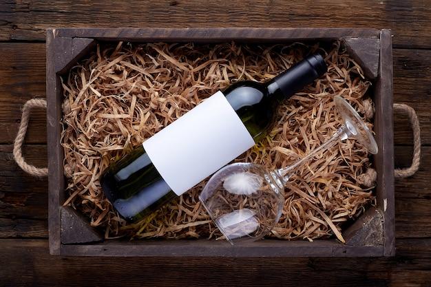 Butelki czerwonego wina zapakowane w otwarte drewniane pudełko