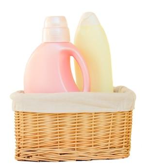 Butelki detergentu do prania w koszu na białym tle