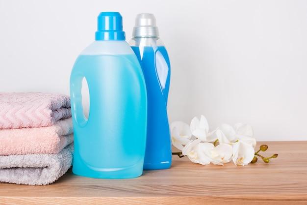 Butelki detergentu i płynu do płukania z czystymi ręcznikami i kwiatami orchidei na drewnianym stole
