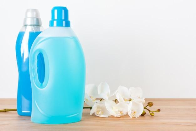 Butelki detergentu i zmiękczacza tkanin z kwiatami orchidei na drewnianym stole