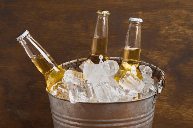 Butelki do piwa pod dużym kątem w wiadrze z kostkami lodu